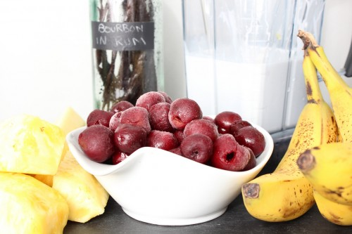 Ingredients for the smoothie include 1/2 of a large pineapple, 3 bananas, roughly 2 cups of frozen cherries, 1 can of full-fat coconut milk, 1/3 can of water (using the empty coconut milk can), and a splash of vanilla extract.